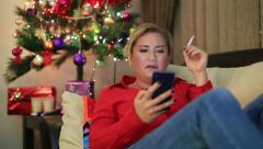Portrait of a sitting on a sofa woman near the christmas tree 25 Stock Footage
