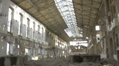 Ruined old large hall with glass roof, broken windows, tilt down, pile of rocks. Stock Footage
