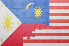 puzzle with the national flag of malaysia and philippines - stock photo