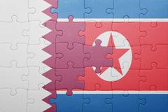 Stock Photo of puzzle with the national flag of north korea and qatar