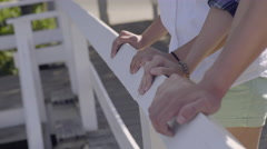 Closeup Of Teens' Hands Leaning Against Bridge Railing, Girl Points To Something Stock Footage