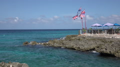 Grand Cayman rocky shore national flags Caribbean 4K Stock Footage