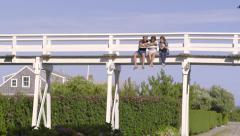 Friends Sit On Bridge, They Take A Selfie Together, Then Chat Stock Footage