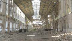 Interior of ruined large factory hall with fallen bricks on the floor, tilt up. Stock Footage