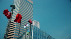 Hong Kong Stock Exchange square with flags, during sunny day. Tilting shot. - stock footage