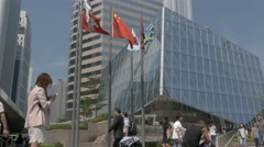 Hong Kong Stock Exchange square with flags and walking people. Flat profile. Stock Footage