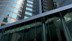 Hong Kong Stock Exchange (HKEx) building with walking people. Tilting shot. Stock Footage