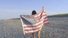 Asian Teen Holds Up American Flag, Wraps It Around Her Body And Walks Down Beach Stock Footage