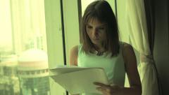 Pretty, young businesswoman writing notes in documents by window Stock Footage