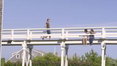 Girls Sit On Bridge, Their Guy Friend Joins Them, High Fives Girl And Sits Down Stock Footage