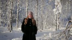 A beautiful woman is happy and walks in the park on a winter day Stock Footage