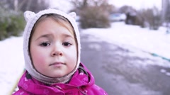 Close-up portrait of 4 year old funny girl with sad face on winter street. Stock Footage