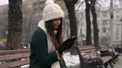 Cute girl sitting on a bench with a mobile phone in winter Stock Footage