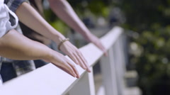 Closeup Of Multiethnic Teens' Hands As They Hold Railing And Walk Across Bridge Stock Footage