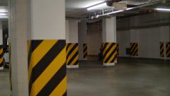 Many cars stand in underground parking with piping and illumination - stock footage