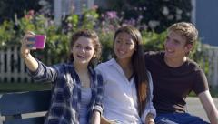 Multiethnic Teen Friends Take Selfies Together On A Bench In A New England Town Stock Footage