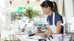 4K Cheerful business owner makes a phone call behind the counter of her shop - stock footage