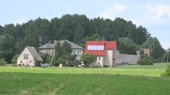 Stock Video Footage of Solar collectors panels on rural village house roof top. Zoom out. 4K