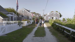 Teens Walk Down Shell Road, Lined With Cottages, In New England Seaside Stock Footage