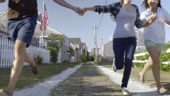 Multiethnic Teens Hold Hands, Run Down Shell Road In New England Seaside Village Stock Footage