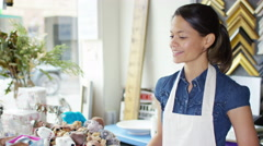 4K Cheerful business owner taking payment from customer in her shop.  - stock footage