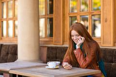Cute smiling female using smartphone in outdoor cafe Stock Photos
