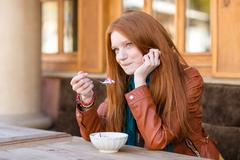 Cute content woman having breakfast and talking on cellphone - stock photo