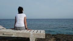Attractive woman admires sea Siting on the shore Stock Footage