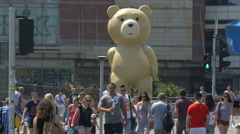 Walking by a statue representing a bear promoting the Ted 2 movie in Warsaw Stock Footage