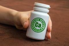 Human hand holding a bottle of pills with calcium on brown background - stock photo