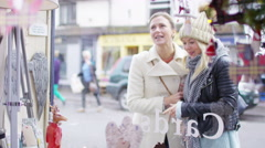 4K 2 cheerful female friends looking in the window of small boutique shop.  Stock Footage