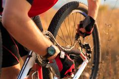 Young man repairing mountain bike in the forest - stock photo