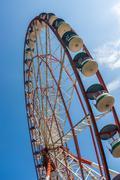 Underside view of a ferris wheel on blue sky background - stock photo