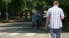 Walking and riding bikes on a street in a park, Warsaw Stock Footage