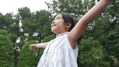 Slow motion of Beautiful little Asian girl enjoy with nature in the park Stock Footage