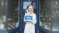 4K Happy female shopkeeper holds up a sign to show she is open for business Stock Footage