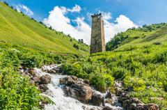 Mountain stream and old watch tower in the village Adishi, Georgia (Svaneti) Stock Photos