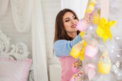 Stock Photo of Model decorating fir-tree