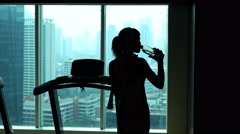 Tired sportswoman drinking water and resting in gym Stock Footage