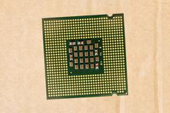 Computer processor chip (CPU) isolated on carton background - stock photo