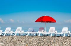 Sun umbrella and beach beds on the shingle beach near sea Stock Photos
