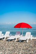 Beach chairs and red umbrella on shingle beach in Batumi Stock Photos