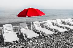 Red sun umbrella and plastic beach beds, black and white concept Stock Photos