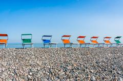 Colorful beach chairs on the shingle beach near sea Stock Photos