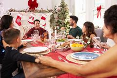 Family With Grandparents Saying Grace Before Christmas Meal - stock photo