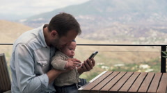 Young father showing something on smartphone his small son on terrace HD Stock Footage