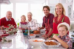 Extended Family Group Basting Christmas Turkey In Kitchen Stock Photos