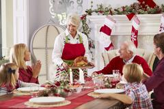 Grandmother Bringing Out Turkey At Family Christmas Meal Stock Photos