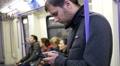 Guy sliding typing smartphone display in subway metro train 4k or 4k+ Resolution