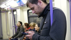 Guy sliding typing smartphone display in subway metro train Stock Footage